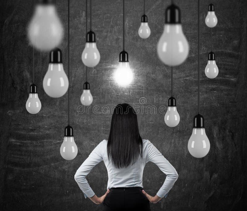 Bakre sikt av brunettdamen som ser de hängande ljusa kulorna ett begrepp av sökande av nya idéer royaltyfri fotografi
