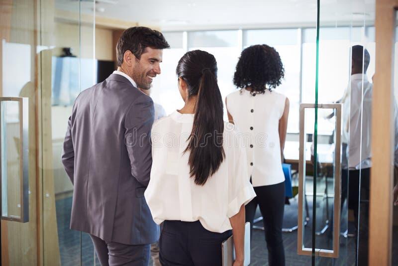 Bakre sikt av Businesspeople som skriver in styrelsen för möte royaltyfria foton