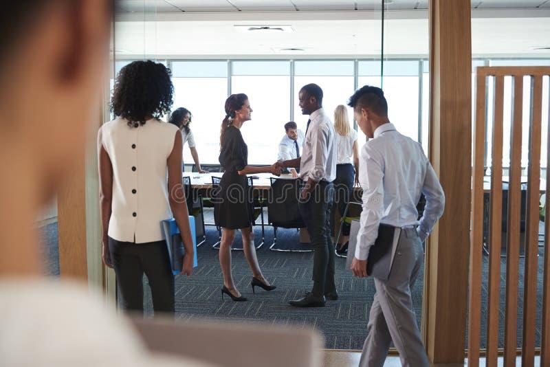Bakre sikt av Businesspeople som skriver in styrelsen för möte arkivbild