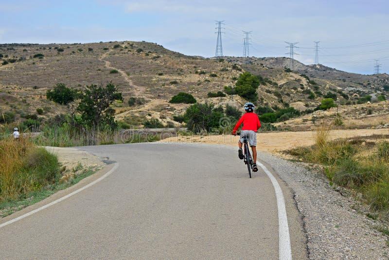 Bakre sikt av cyklisten som rider upp en kulle arkivfoto