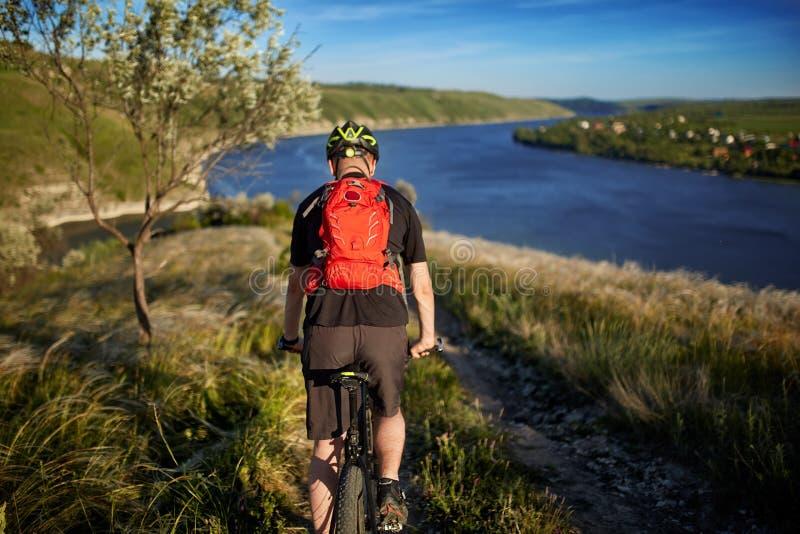 Bakre sikt av cyklistridningen med mountainbiket på slingan ovanför floden royaltyfri foto