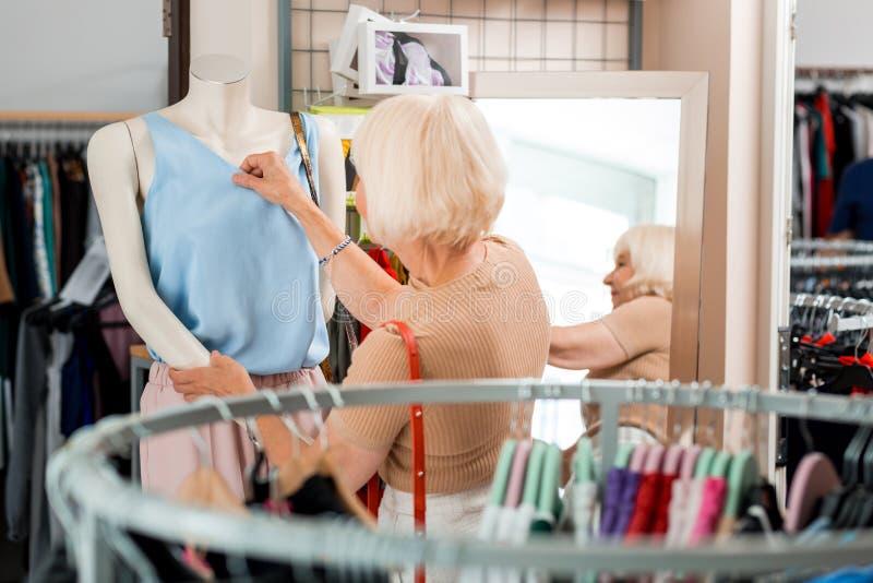 Bakre sikt av den äldre eleganta kvinnan som kontrollerar kläder som är kvalitets- på shoppinglagret royaltyfria foton