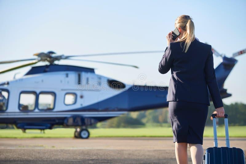 Bakre sikt av den affärskvinnaWalking Towards Helicopter stunden Tal arkivbilder