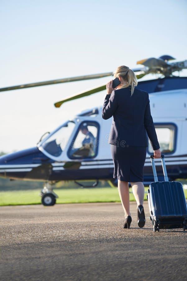 Bakre sikt av den affärskvinnaWalking Towards Helicopter stunden Tal royaltyfri foto