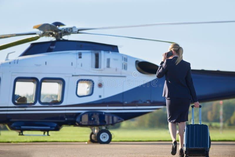 Bakre sikt av den affärskvinnaWalking Towards Helicopter stunden Tal fotografering för bildbyråer