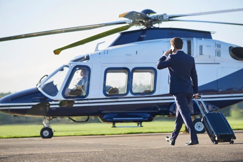 Bakre sikt av den affärsmanWalking Towards Helicopter stunden Talki arkivbilder