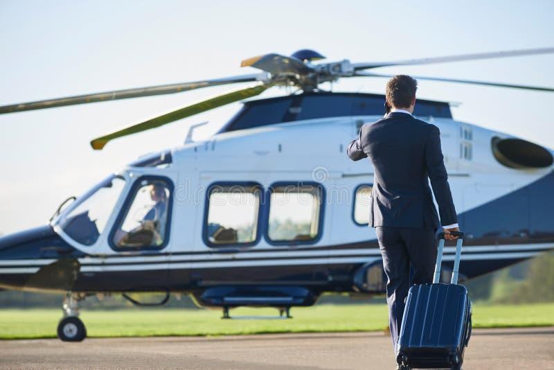 Bakre sikt av den affärsmanWalking Towards Helicopter stunden Talki arkivbild
