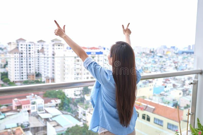 Bakre sikt av den aktiva sportiga kvinnan som str?cker p? balkong arkivfoton