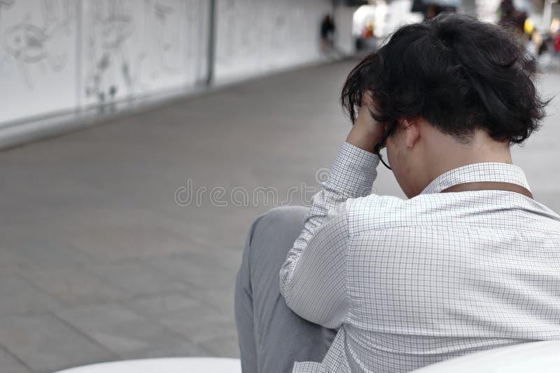 Bakre sikt av den angelägna överansträngde unga asiatiska affärsmannen som sitter och trycker på pannan med händer royaltyfri fotografi