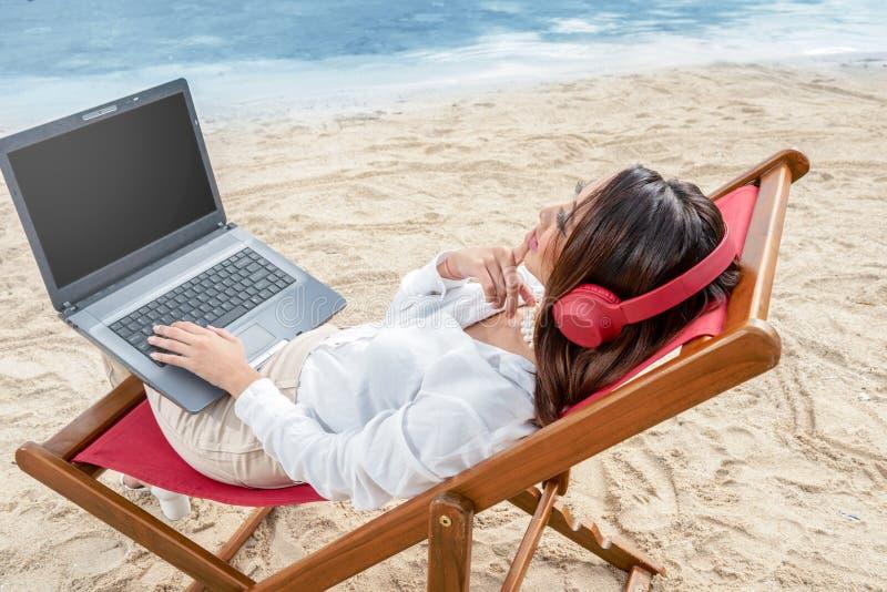 Bakre sikt av den asiatiska affärskvinnan som arbetar med bärbar datorstund genom att använda hörlurar som sitter i strandstolen  royaltyfri bild