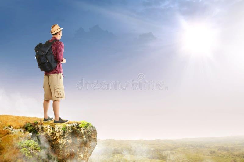 Bakre sikt av den asiatiska handelsresandemannen med hatt- och ryggsäckanseende på kanten av klippan som ser landskap royaltyfri foto