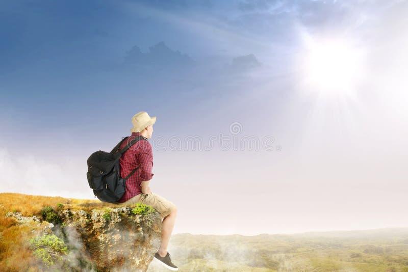 Bakre sikt av den asiatiska handelsresandemannen med hatten och ryggsäcken som sitter på kanten av klippan som ser landskap arkivfoto
