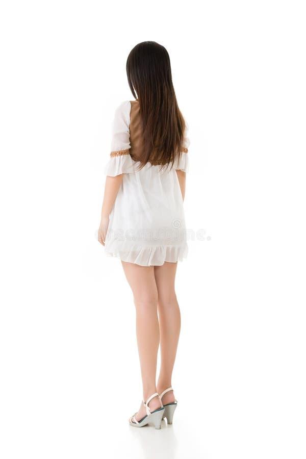 Bakre sikt av den asiatiska kvinnan med den vita korta klänningen arkivfoto
