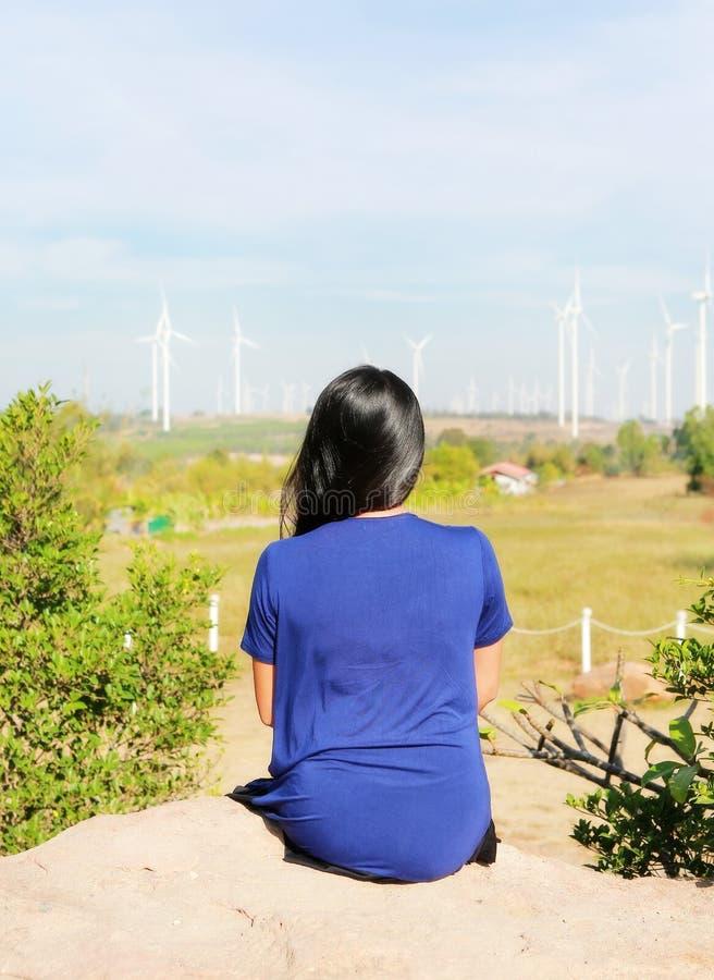 Bakre sikt av den asiatiska kvinnan mot fält för vindturbin royaltyfria foton