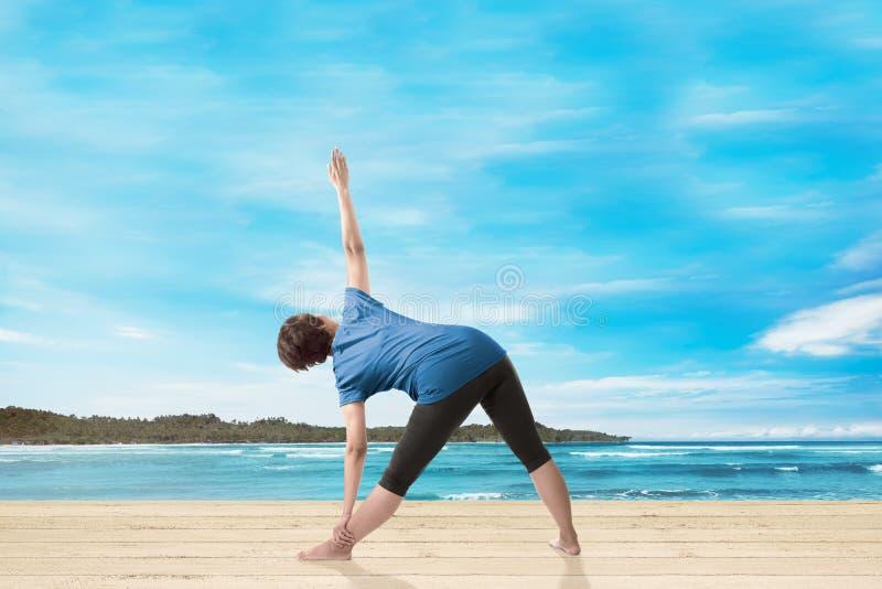Bakre sikt av den asiatiska kvinnan som gör yoga royaltyfria foton