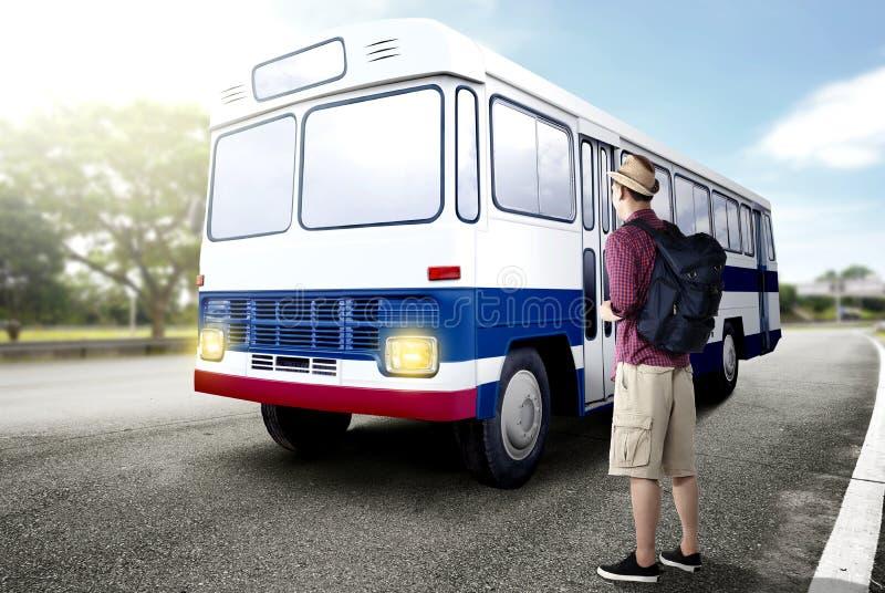 Bakre sikt av den asiatiska mannen i hatt med ryggsäcken som står och väntar en buss på vägen arkivbild