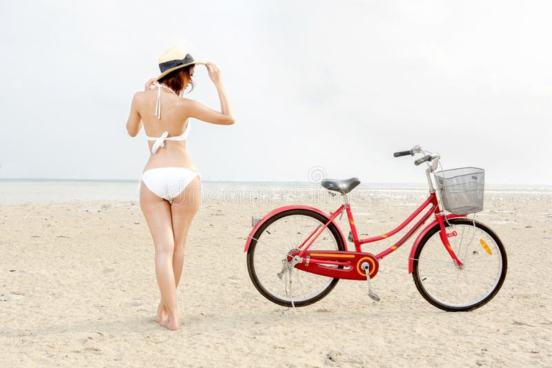 Bakre sikt av den asiatiska sexiga flickan med hatten och bikinin med cykeln på stranden fotografering för bildbyråer