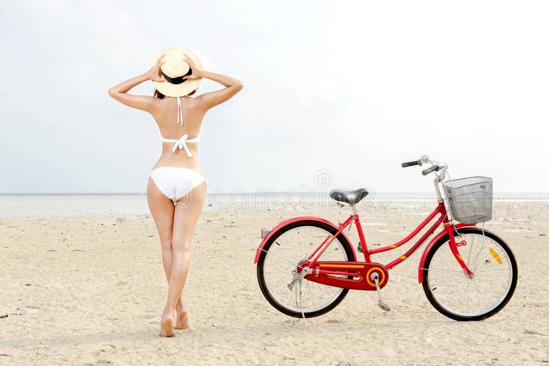 Bakre sikt av den asiatiska sexiga flickan med hatten och bikinin med cykeln p? stranden royaltyfri foto