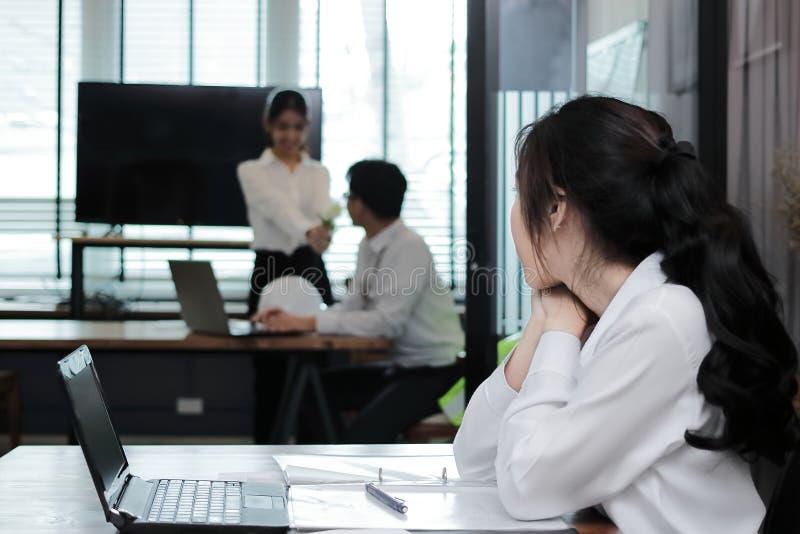 Bakre sikt av den avundsjuka asiatiska affärskvinnan som ser förälskade tillgivna par Avundsjuka och avund i vänförhållande royaltyfri foto