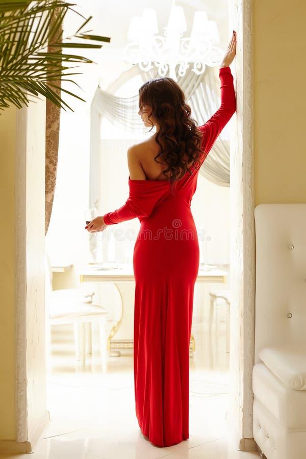 Bakre sikt av den eleganta kvinnan med exponeringsglas av vin royaltyfria foton