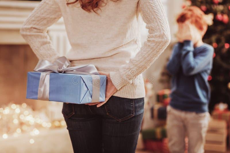 Bakre sikt av den försiktiga modern som rymmer en gåva för hennes son arkivfoto