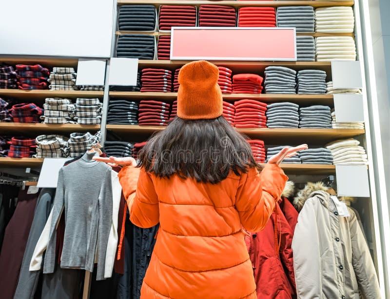 Bakre sikt av den förvirrade kvinnan som gör en gest händer till sidan, medan se kläder som visas i lager Mycket varmt fotografering för bildbyråer