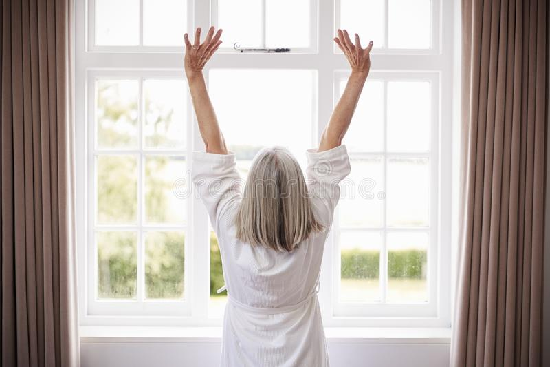 Bakre sikt av den höga kvinnan som sträcker i Front Of Bedroom Window fotografering för bildbyråer