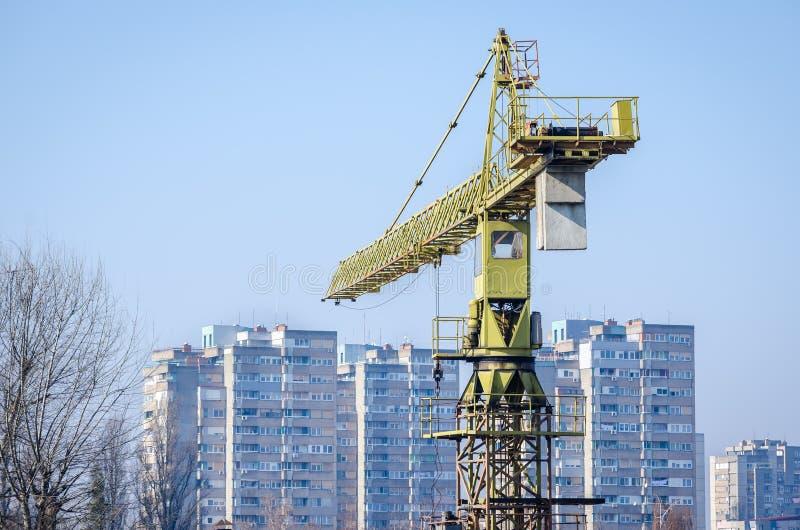 Bakre sikt av den högväxta konstruktionskranen i den stads- stadsplatsen med bostads- byggnader i bakgrunden royaltyfri bild