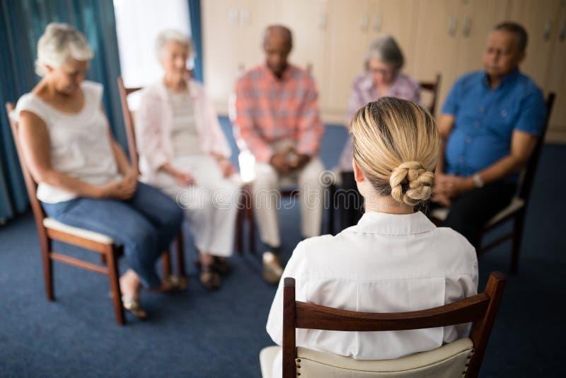 Bakre sikt av den kvinnliga doktorn som mediterar med högt folk arkivbilder