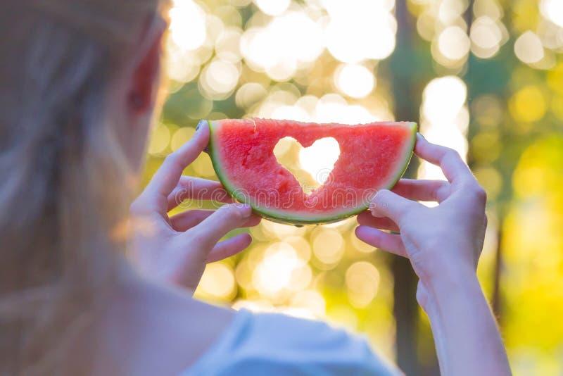 Bakre sikt av den kvinnliga hållande vattenmelon med hjärtaformhålet i natur royaltyfria foton