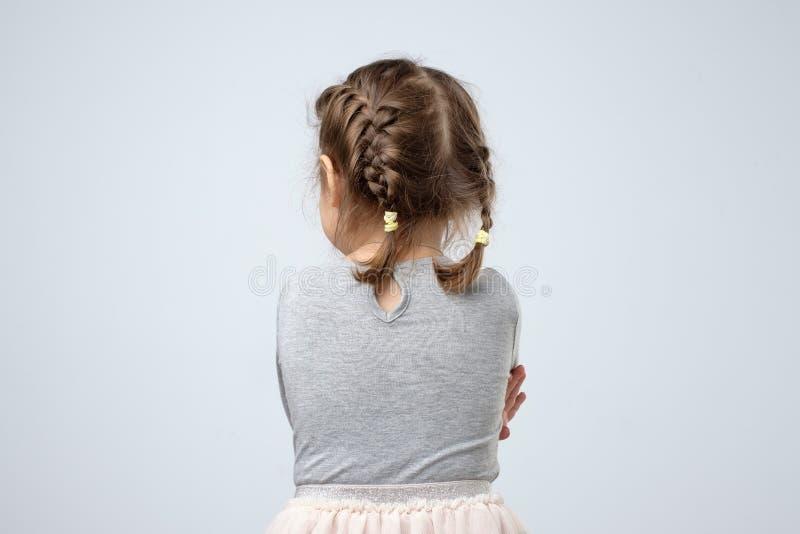 Bakre sikt av den lilla caucasian flickan Ungen förloras eller kränks på föräldrar arkivbilder
