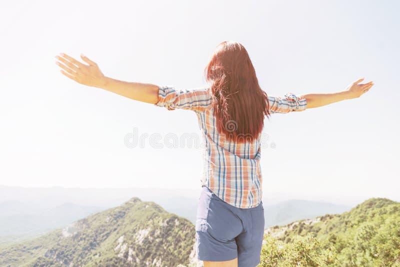 Bakre sikt av den lyckliga kvinnan för frihet som är utomhus- i sommar arkivfoto