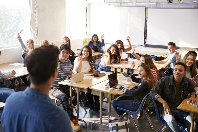 Bakre sikt av den manliga h?gstadiuml?raren Standing At Front Of Class Teaching Lesson fotografering för bildbyråer