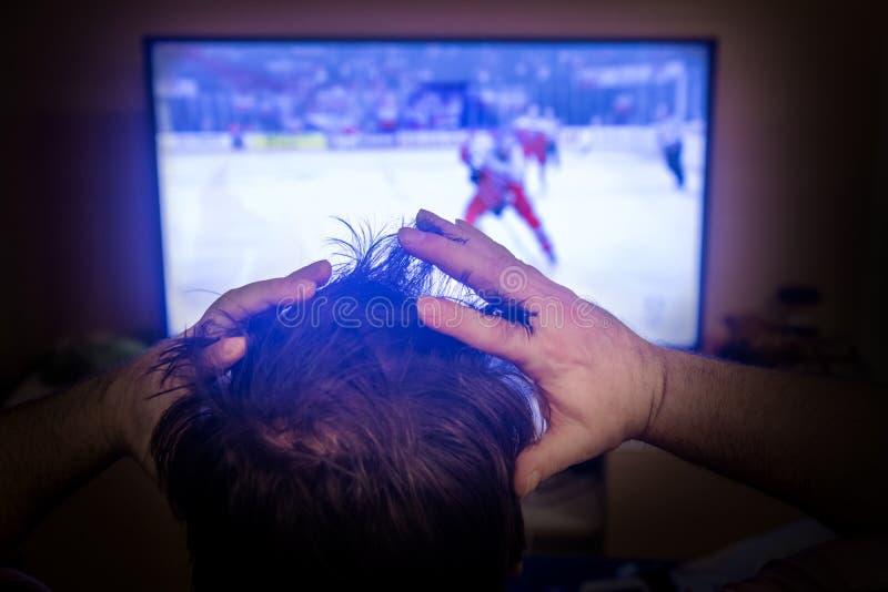 Bakre sikt av den manliga head hållande ögonen på sporten i TV arkivfoton