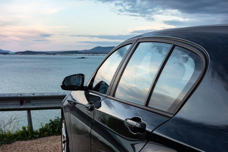 Bakre sikt av den moderna lyxiga svarta bilen som parkeras ovanför havet med en romantisk sikt under solnedgången royaltyfri bild