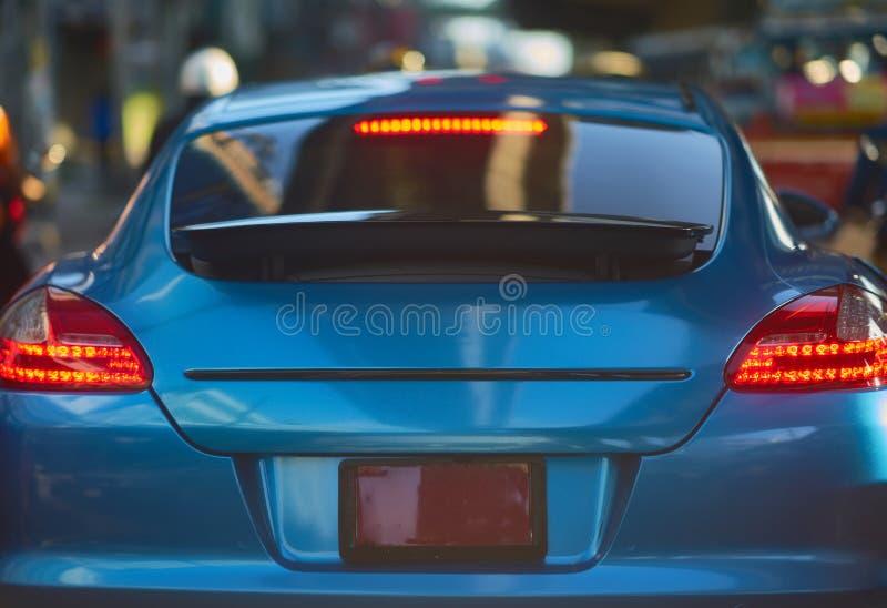 Bakre sikt av den nya sportbilen på trafikgatabakgrund arkivfoton