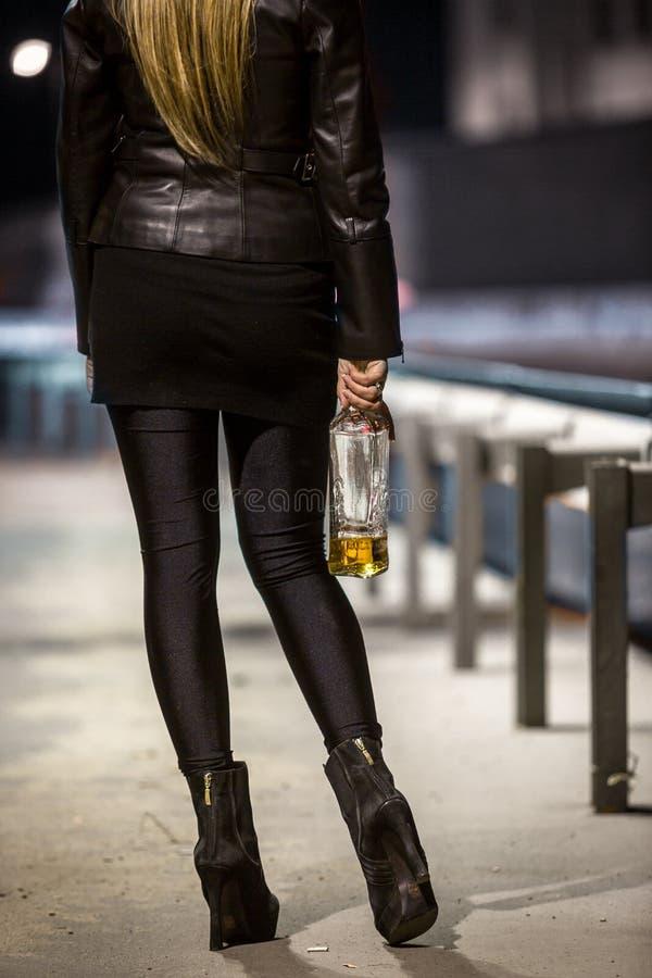 Bakre sikt av den sexiga kvinnan som poserar på gatan med whisky arkivbilder