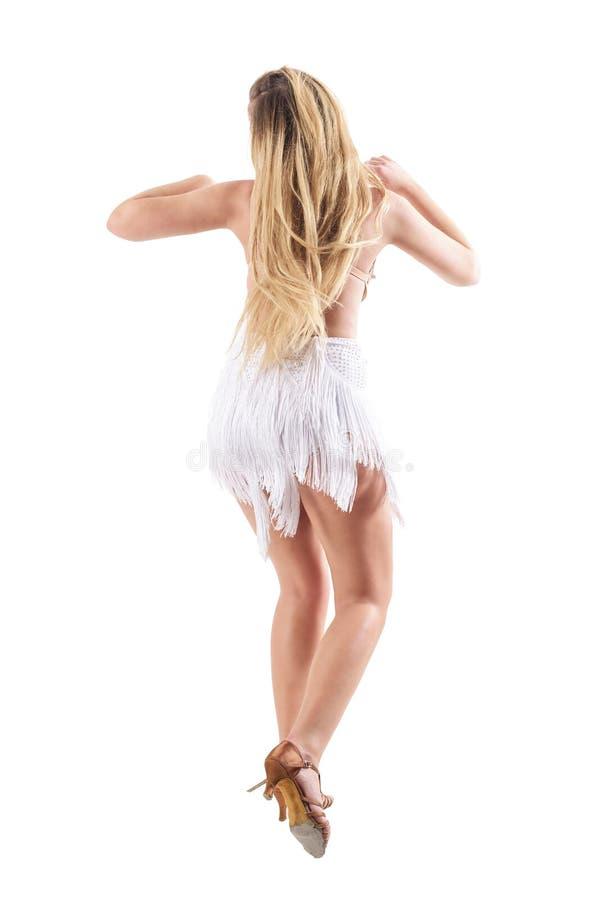 Bakre sikt av den sinnliga bekymmerslösa driftiga långa hårkvinnadansen royaltyfri foto
