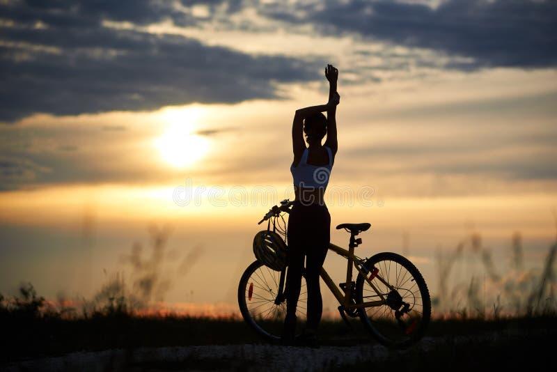 Bakre sikt av den sportiga flickan för kontur som står nära cykeln mot bakgrundsaftonhimmel arkivbilder