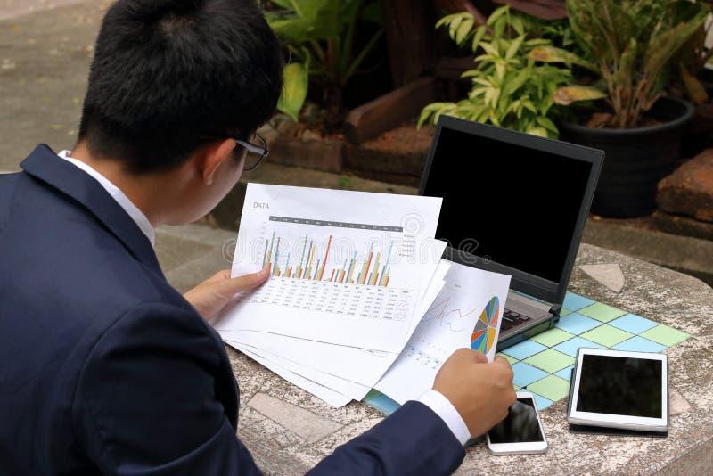 Bakre sikt av den stiliga affärsmannen som ser dokumentdiagram och utomhus tänker om hans jobb i parkera arkivbild