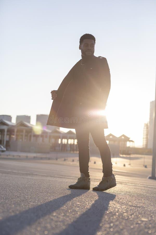 Bakre sikt av den svarta unga skäggiga mannen som utomhus går, medan se bort royaltyfri bild