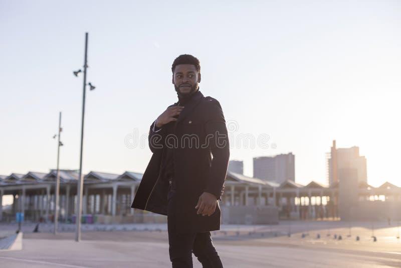 Bakre sikt av den svarta unga skäggiga mannen som utomhus går, medan se bort fotografering för bildbyråer