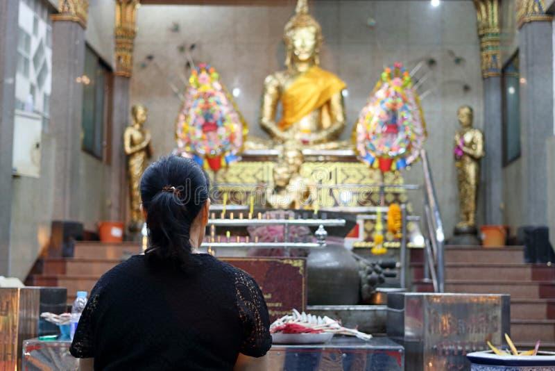 Bakre sikt av den thailändska kvinnan som ber till Buddha i templet royaltyfri bild