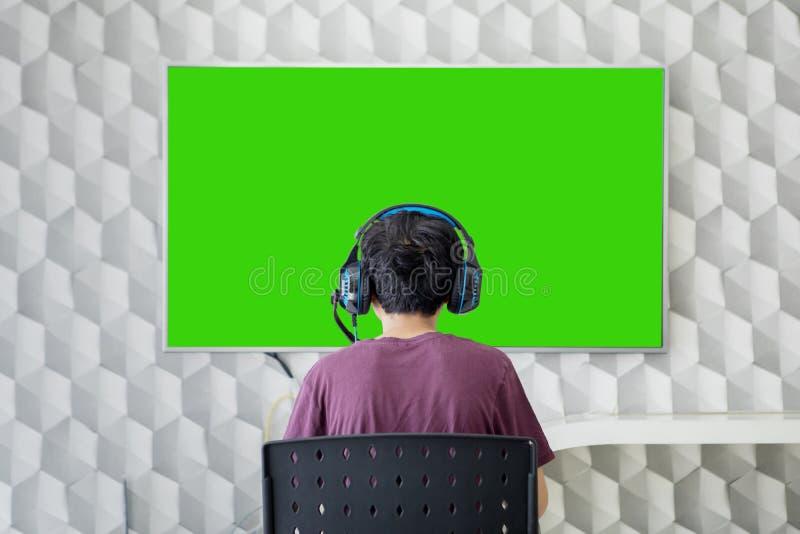 Bakre sikt av den tonåriga pojken som spelar videospel royaltyfri bild