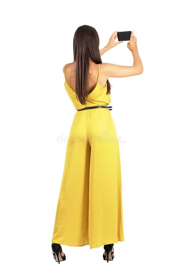 Bakre sikt av den unga eleganta kvinnan som tar fotoet med smartphonen arkivfoton