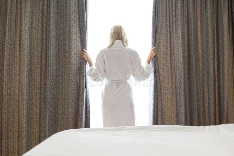 Bakre sikt av den unga kvinnan i gardiner för badrocköppningsfönster på hotellrum arkivbild