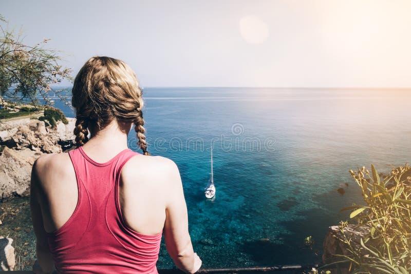 Bakre sikt av den unga kvinnan i sportswearen som ser havet arkivfoto