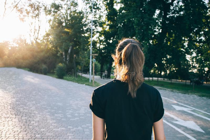 Bakre sikt av den unga kvinnan som bär den svarta t-skjortan som går ner arkivfoton