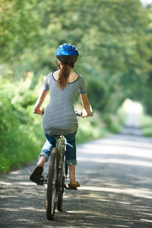 Bakre sikt av den unga kvinnan som cyklar på landsgränd royaltyfria bilder