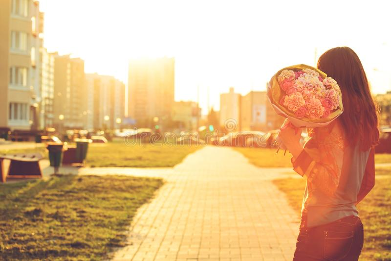 Bakre sikt av den unga kvinnan som mottar en härlig bukett av rosa färger p royaltyfri foto